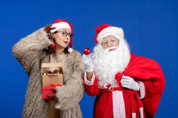 Widok z przodu święty mikołaj z młodą kobietą trzymającą torbę z prezentami i zabawkami na niebieskim świątecznym świątecznym nowym roku