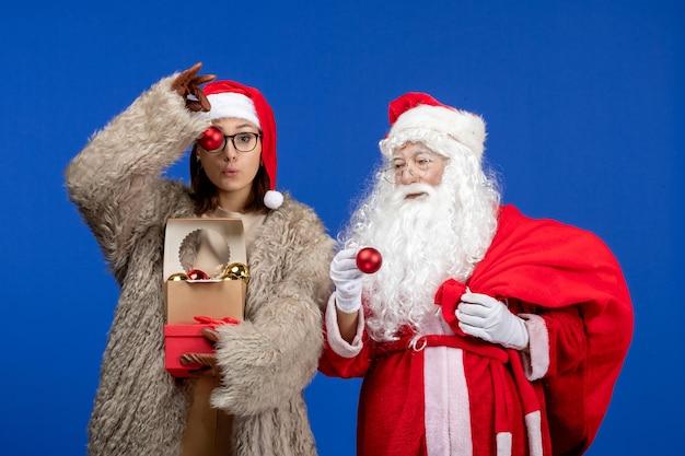 Widok z przodu święty mikołaj z młodą kobietą trzymającą torbę z prezentami i zabawkami w niebieskich świątecznych kolorach nowy rok