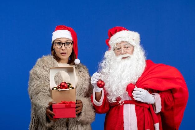 Widok z przodu święty mikołaj z młodą kobietą trzymającą torbę z prezentami i zabawkami w niebieskim kolorze świątecznym