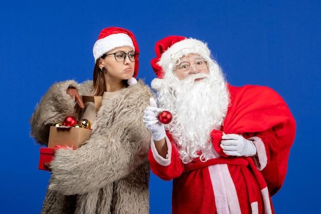 Widok z przodu święty mikołaj z młodą kobietą trzymającą torbę z prezentami i zabawkami w niebieskim świątecznym kolorze nowego roku