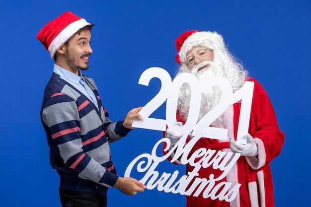 Widok z przodu święty mikołaj z młodym mężczyzną trzymającym i wesołych świątecznych pism na niebieskim nowym roku obecnych świąt