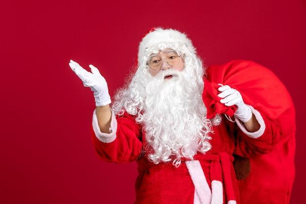 Widok z przodu święty mikołaj z torbą pełną prezentów na czerwone emocje świąteczne nowy rok bożego narodzenia