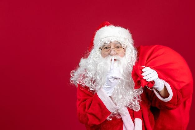 Widok z przodu święty mikołaj z torbą pełną prezentów na czerwonych świątecznych emocjach świątecznych nowego roku