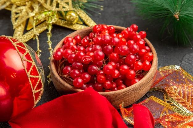 Widok z przodu świeża czerwona żurawina wokół świątecznych zabawek na ciemnym tle kolor świąteczna świąteczna owocowa jagoda