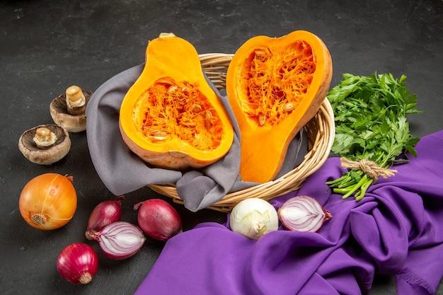 Widok z przodu świeża dynia z cebulą i zieleniną na ciemnym stole dojrzała roślina spożywcza koloru