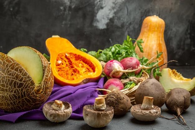 Widok z przodu świeża dynia z rzodkiewką i zielenią na ciemnym stole dojrzałe kolorowe jedzenie