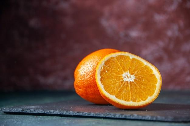 Widok z przodu świeża pokrojona pomarańcza na ciemnym tle dojrzały sok owocowy o łagodnym kolorze cytrusowy smak cytrusowy