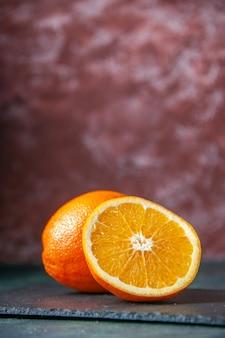Widok z przodu świeża pokrojona pomarańcza na ciemnym tle dojrzały sok owocowy w kolorze soku cytrusowego drzewo cytrusowe
