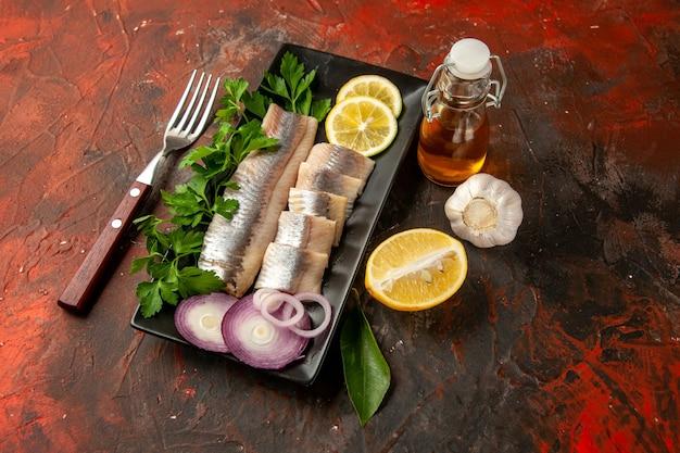 Widok z przodu świeża pokrojona ryba z zieleniną cytryną i cebulą wewnątrz czarnej patelni na ciemnym zdjęciu kolor owoców morza z przekąskami?