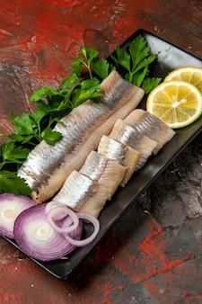 Widok z przodu świeża pokrojona ryba z zieleniną i cebulą w czarnej patelni na ciemnym zdjęciu z przekąskami w kolorze mięsa