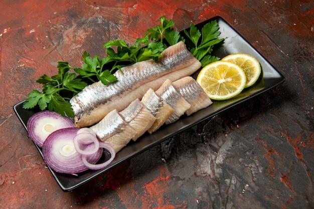 Widok z przodu świeża pokrojona ryba z zieleniną i cebulą wewnątrz czarnej patelni na ciemnej przekąsce mięso kolorowy posiłek owoce morza zdjęcie