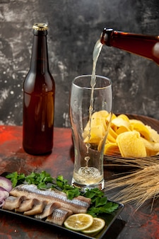 Widok z przodu świeża pokrojona ryba z zieleniną i piwem na ciemnym zdjęciu kolor owoców morza przekąska posiłek mięsny