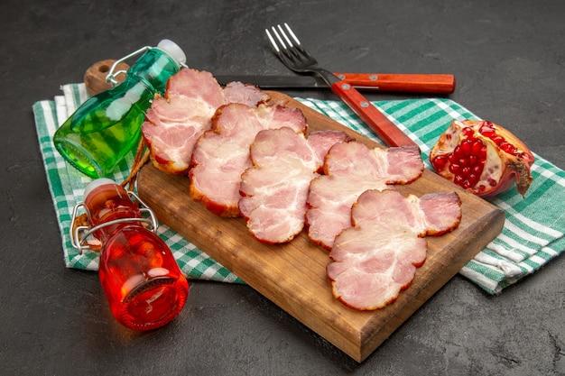 Widok z przodu świeża pokrojona szynka na drewnianym biurku i szara żywność w kolorze surowej świni
