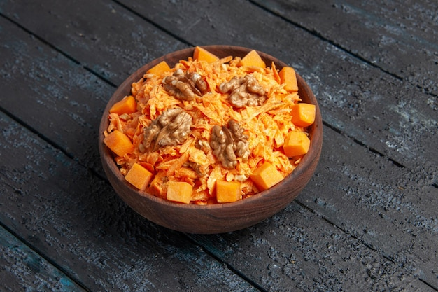 Widok z przodu świeża sałatka z marchwi tarta sałatka z orzechami włoskimi i czosnkiem na ciemnej podłodze dieta dojrzała sałatka zdrowy kolor