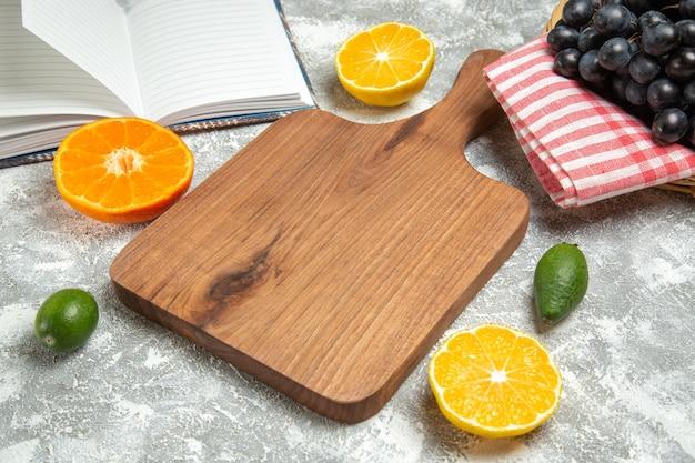 Widok z przodu świeże ciemne winogrona z pomarańczami na białym tle dojrzałe owoce łagodne drzewo świeża witamina