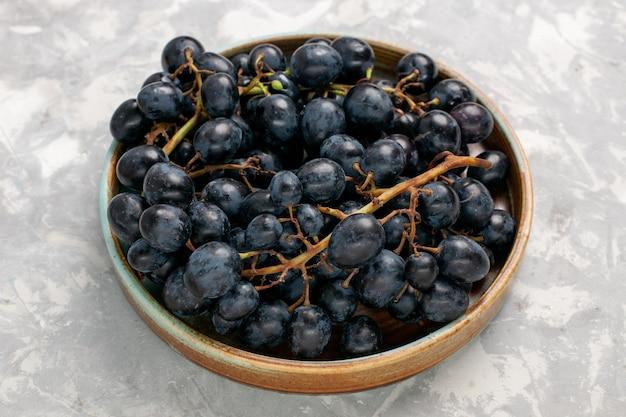 Widok z przodu świeże czarne winogrona soczyste łagodne słodkie owoce na jasnym białym biurku owoce świeży łagodny sok wino