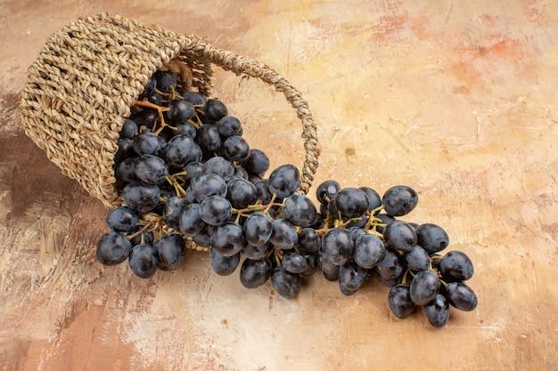 Widok z przodu świeże czarne winogrona wewnątrz kosza na jasnym biurku dojrzałe wino owocowe łagodne zdjęcie