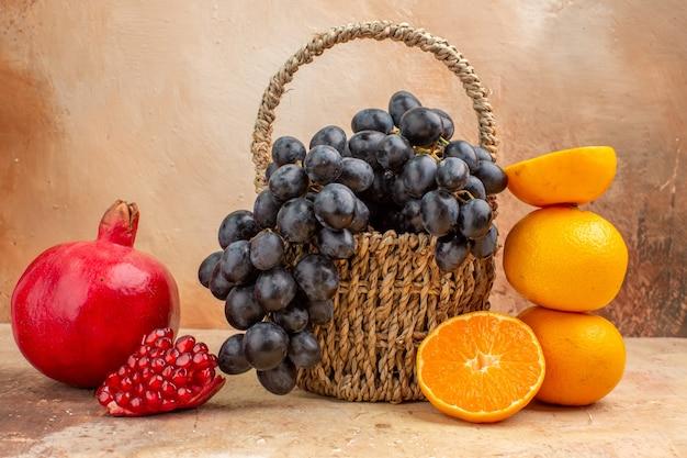 Widok z przodu świeże czarne winogrona z pomarańczą na jasnym tle łagodne drzewo zdjęcia dojrzałe owoce witamina