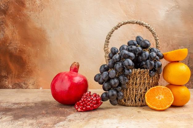Widok z przodu świeże czarne winogrona z pomarańczą na jasnym tle łagodne zdjęcie dojrzałe owoce witaminy drzewo
