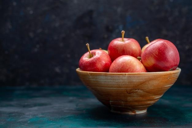 Widok z przodu świeże czerwone jabłka soczyste i łagodne wewnątrz talerza na granatowym biurku owoce świeża, łagodna witamina