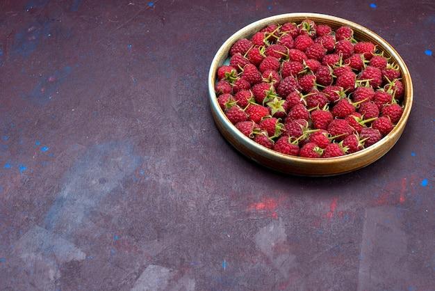 Widok z przodu świeże czerwone maliny dojrzałe i kwaśne jagody na ciemnoniebieskim tle owoce jagodowe łagodny letni witamina żywności
