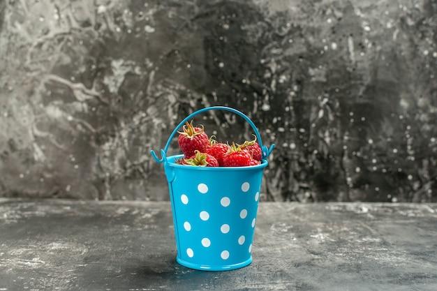 Widok z przodu świeże czerwone maliny w koszyczku na szarych owocach kolor żurawina dzika fotografia jagoda