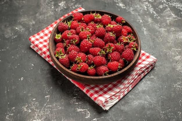 Widok z przodu świeże czerwone maliny wewnątrz talerza na szarym owocowym kolorze jagodowym żurawinowym dzikim zdjęciu