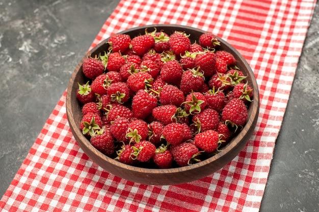 Widok z przodu świeże czerwone maliny wewnątrz talerza na szarym zdjęciu kolor owoców jagodowych żurawina dzika
