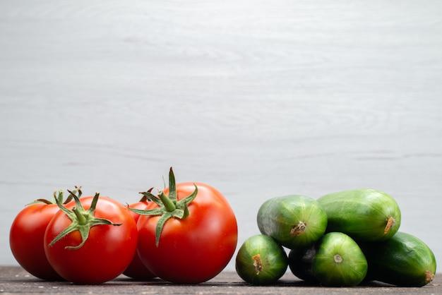 Widok z przodu świeże czerwone pomidory dojrzałe wraz z zielonymi ogórkami na biały, warzywny posiłek