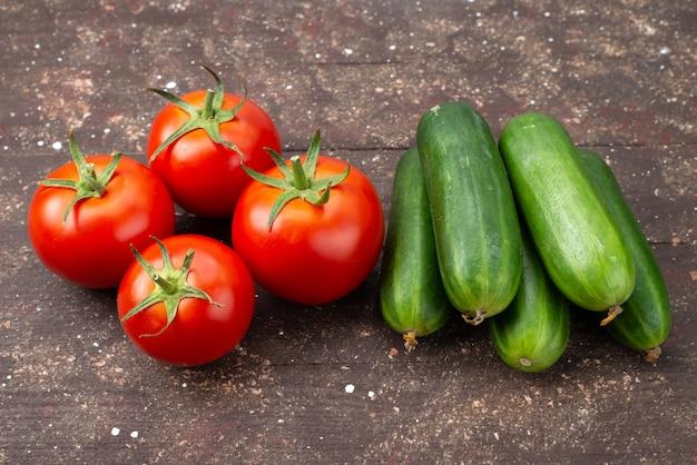 Widok z przodu świeże czerwone pomidory dojrzałe wraz z zielonymi ogórkami na brązowym, warzywnym posiłku