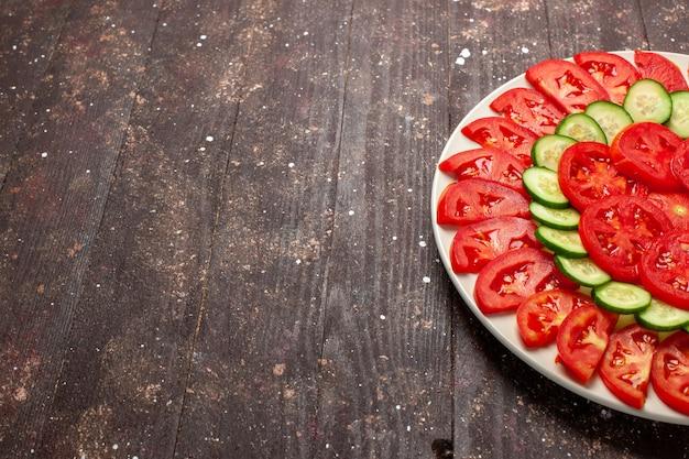 Widok z przodu świeże czerwone pomidory pokrojone świeże sałatki na brązowym biurku