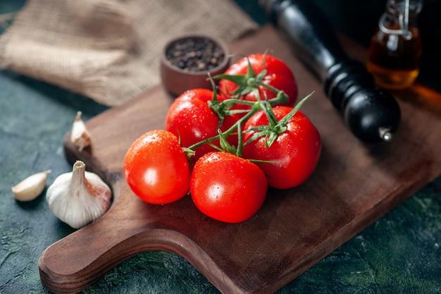Widok z przodu świeże czerwone pomidory z czosnkiem na ciemnym tle