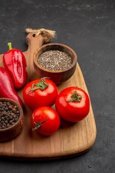 Widok z przodu świeże czerwone pomidory z przyprawami na ciemnej przestrzeni