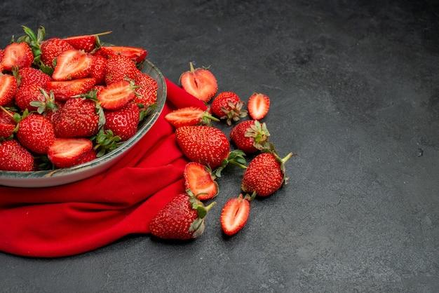 Widok z przodu świeże czerwone truskawki wewnątrz talerza na ciemnym tle dzikie jagody lato kolor sok z drzewa wolne miejsce na tekst