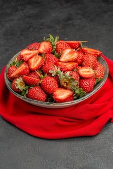 Widok z przodu świeże czerwone truskawki wewnątrz talerza na ciemnym tle jagoda lato kolor sok z drzewa dziki