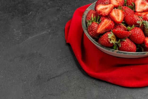 Widok z przodu świeże czerwone truskawki wewnątrz talerza na ciemnym tle letni kolor sok z drzewa jagoda dzika wolna przestrzeń