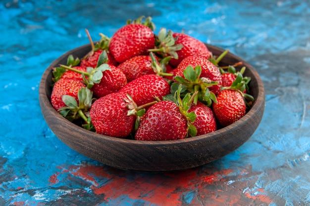 Widok z przodu świeże czerwone truskawki wewnątrz talerza na niebieskim tle kolor owoców jagodowych vitamine