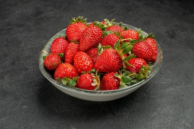 Widok z przodu świeże czerwone truskawki wewnątrz talerza na szarym tle sok z drzewa kolor dziki smak jagody lato
