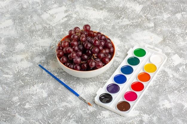Widok z przodu świeże czerwone winogrona z farbami na białej powierzchni