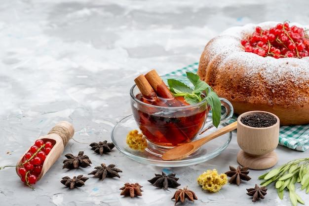 Widok z przodu świeże czerwone żurawiny kwaśne i łagodne z okrągłym ciastem, herbatą i cynamonem na białym biurku owoce jagodowe