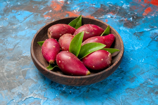 Widok z przodu świeże dojrzałe śliwki wewnątrz drewnianego talerza na niebieskim tle kolor drzewa kwaśne owoce łagodne