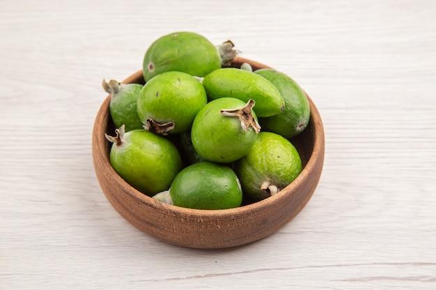 Widok z przodu świeże feijoas wewnątrz talerza na białym tle kolor owoców tropikalna dojrzała dieta egzotyczna