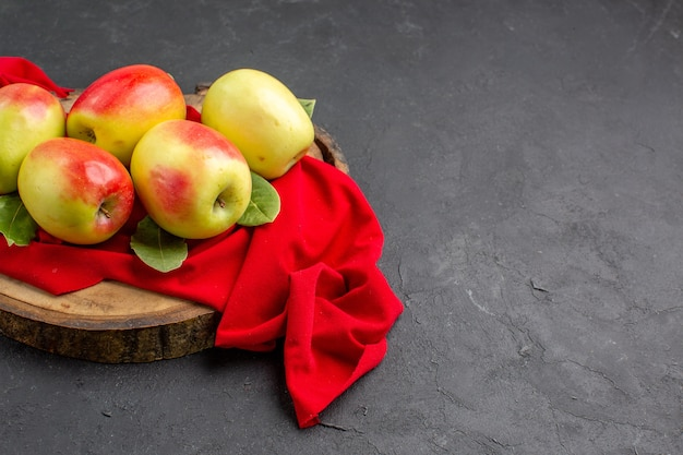 Widok z przodu świeże jabłka dojrzałe owoce na czerwonej tkance i szarej podłodze świeże dojrzałe drzewo owocowe