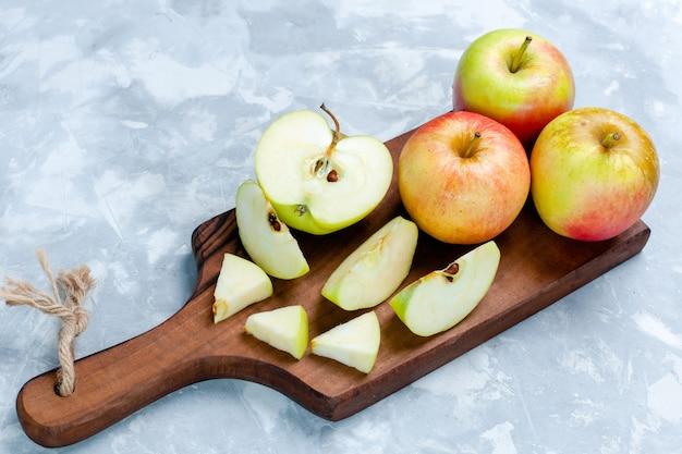 Widok z przodu świeże jabłka pokrojone i całe owoce na jasnobiałej powierzchni owoce świeża, łagodna dojrzała witamina