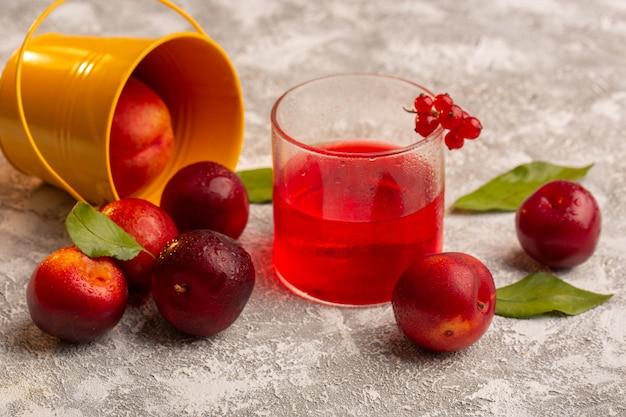 Widok z przodu świeże kwaśne śliwki z biurkiem z czerwonym sokiem śliwkowym