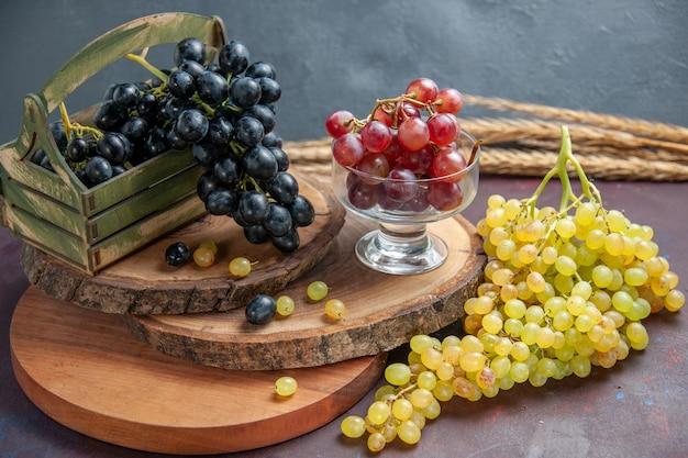 Widok z przodu świeże, łagodne winogrona ciemne i zielone owoce na ciemnej powierzchni wino świeża dojrzała roślina winogronowa
