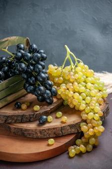 Widok z przodu świeże, łagodne winogrona ciemne i zielone owoce na ciemnej powierzchni wino winogronowe owoce dojrzałe świeża roślina drzewna