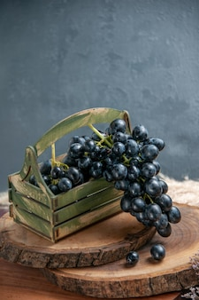 Widok z przodu świeże, łagodne winogrona ciemne owoce na ciemnej powierzchni wino winogronowe owoce dojrzałe świeże rośliny drzewne