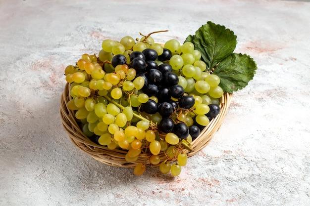 Widok z przodu świeże, łagodne winogrona w koszu na białej przestrzeni