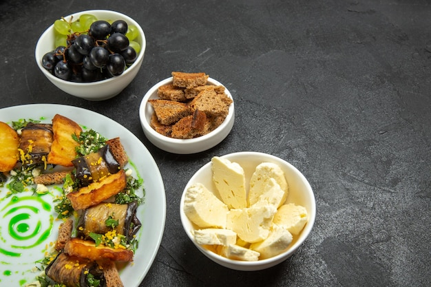 Widok z przodu świeże, łagodne winogrona z bułeczkami z białego sera z bakłażanem i krojonym chlebem na ciemnym tle posiłek jedzenie danie mleko owoce